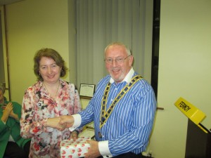 Mary Whelan receives her prize as Humorous Contest Runner-up with warm applause.