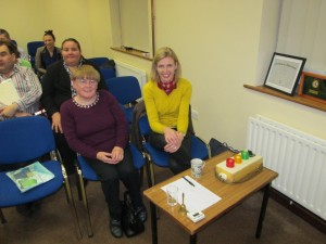 Keeping An Eye On Time:- Area Governor Johanna Hegarty (left) and Michelle O'Brien share the role of Timekeeper at the Club meeting of November 3rd 2015. To the right can be seen the system of lights that govern the duration of speeches: the green comes on at five minutes; amber at six; red at seven by which time the speaker should be wrapping things up. In competition there is just a thirty second period of grace after the red light beyond which the speaker is automatically disqualified.