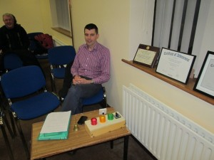 Padraig Murphy acts as Timekeeper at the meeting of November 17th 2015. It is a task that requires precision and attentiveness, a vital role that often does not receive the recognition it deserves. The sheet on the table to the left of picture contains the duration of every speech made and of the length of every phase of the meeting. This is read out when it comes to the General Evaluation before the conclusion of proceedings. The set of lights in front of Padraig govern the length of speeches. The normal time allowed is seven minutes: the green comes on at five, the amber at six and the red at seven, when the speaker should be wrapping things up at that stage. The Toastmasters' ideal is to impart as much information with an elegant economy of words within that spare timeframe. In competition, speakers who go beyond the thirty second period of grace after the coming on of the seventh minute red light, are disqualified. Of course, for some more advanced presentations the time limits are extended and appropriate adjustments are made beforehand with the Timekeeper. The bell on the table is normally used in the impromptu Topics session; it rings after the speaker has completed the allowed two minutes, and again after one minute add-ons by other contributors.