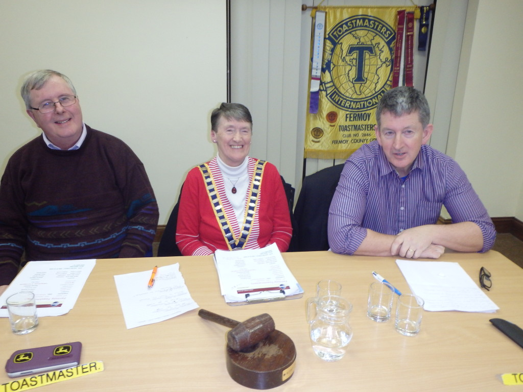 The Top Table:- Club President Eilish Ui Bhriain flanked by Toastmaster of the evening Jerry Hennessy (left|) and Topicsmaster Frank O' Driscoll with the club banner partially seen in the background. Dating from 1970 we are now within a few short years of celebrating the Golden Jubilee of our Charter in 2020.