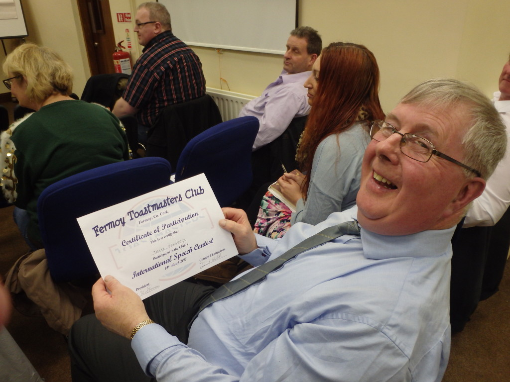 Jerry Hennessy looks up with a warm smile after receiving his Certificate of Participation in the March 14th Club Speech contest.