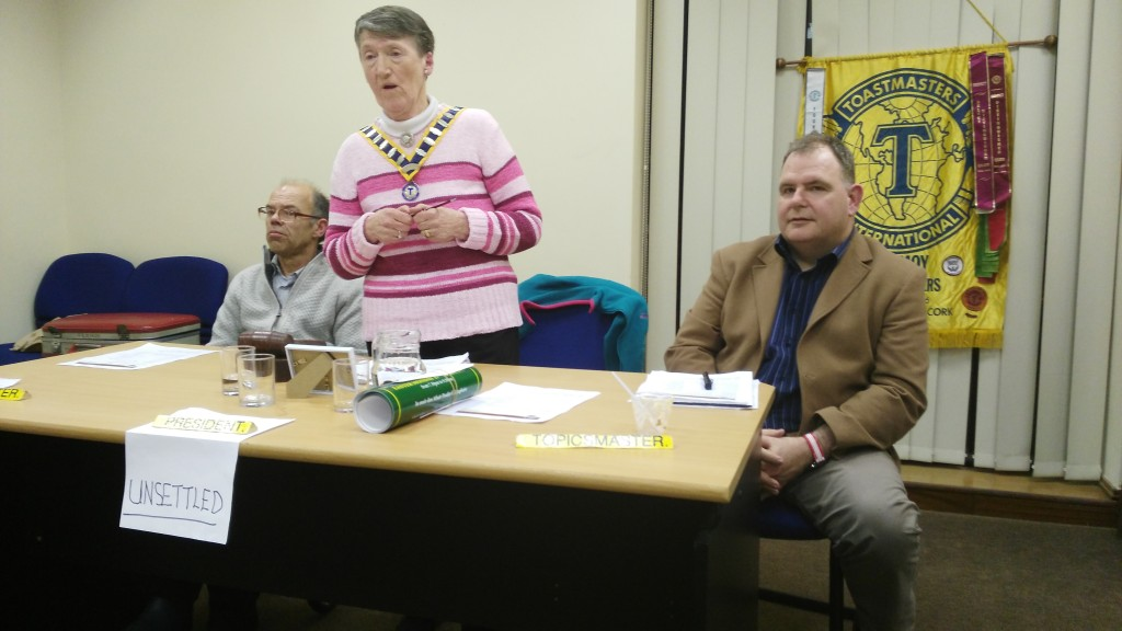 The Top Table at the Club Meeting of April 11th 2017. President Eilish Ui Bhriain extends a warm welcome to all flanked by the vastly experienced and one of our most dedicated mambers Michael Sheehan, Toastmaster of the evening (left) and Conor MacAree about to make his impressive debut as Topicsmaster, with the Club Banner in the background. The prominently displayed word 'Unsettled', refers not to the weather at the time or still less to the mood of the evening, but rather the choice of word by the Wordmaster. There is a different word for each meeting with a different Wordmaster every time. Count is kept of the number of times members and contributors use the chosen world throughout.