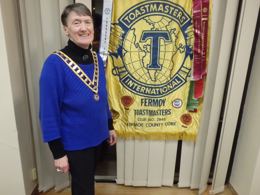 President of Fermoy Toastmasters Eilish Ui Bhriain proudly stands beside the Club Banner received in 1970, the visible symbol of almost half a century in which this club has played a unique and outstanding part in the social, cultural and recreational life of our community, touching and enriching the lives of countless people. Long may it so continue!