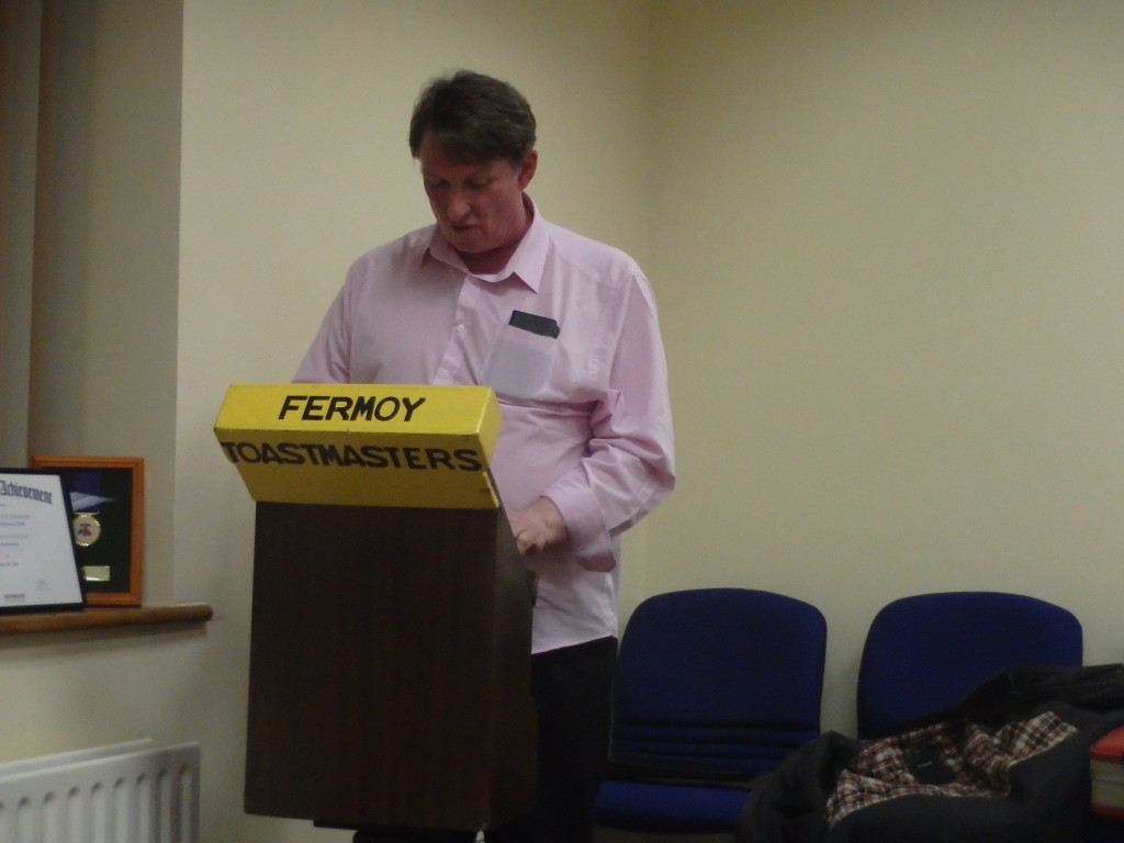 Tim Fitzgerald stands at the lectern delivering his overall impression as General Evaluator of the meeting.
